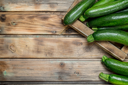 Green zucchini in wooden tray. On wooden background