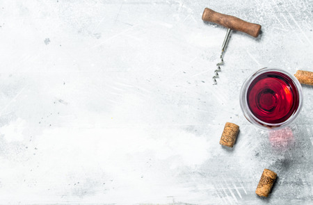Wine background. A glass of red wine and a corkscrew. On a rustic background.