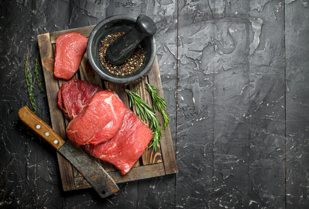 Raw meat. Fresh beef on a wooden tray with fragrant peppercorn and rosemary branches. On a black rustic background. Standard-Bild - 118731139