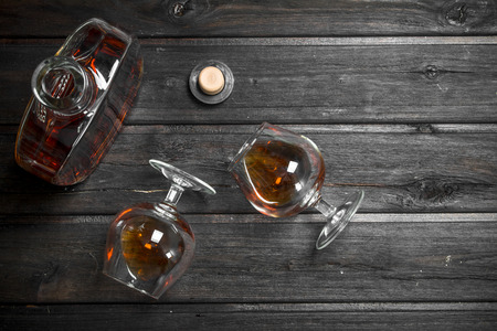 Cognac in a glass bottle and glasses. On black wooden background