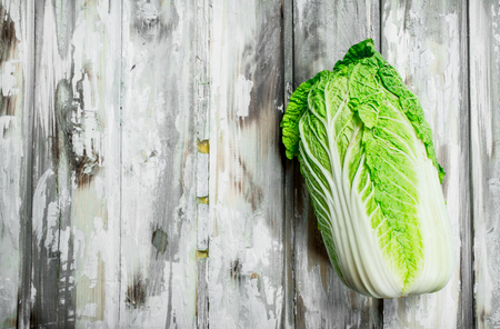 A whole cabbage. On a wooden background.