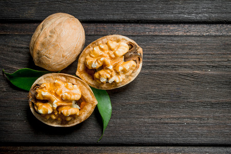 Peeled walnut with leaves . On a wooden background.