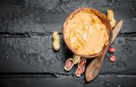 Peanut butter in bowl with wooden spoon . On black rustic background.