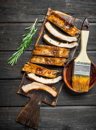 Sliced grilled ribs with sauce. On a wooden background.