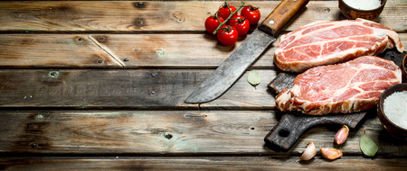 Raw pork steaks with tomatoes and spices. On a wooden background. Stock Photo