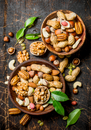 Different types of nuts in bowls with green leaves. On a wooden background.