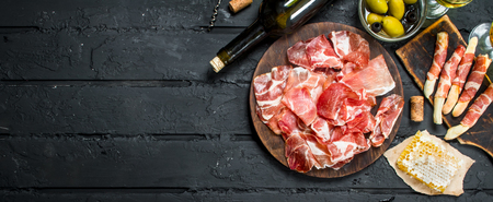 Spanish ham with red wine and breadsticks. On black rustic background. Standard-Bild