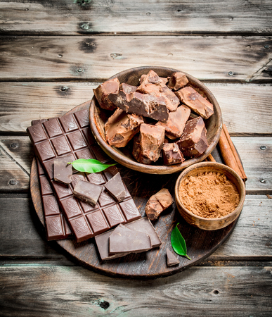 Chocolate in a bowl with cocoa powder on the Board. On a wooden background.