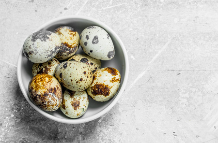 Quail eggs in the bowl. On a rustic background.