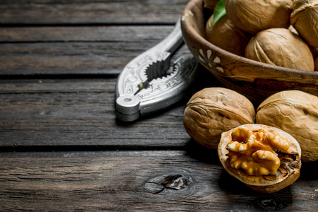 Shelled walnuts with a Nutcracker. On a wooden background.