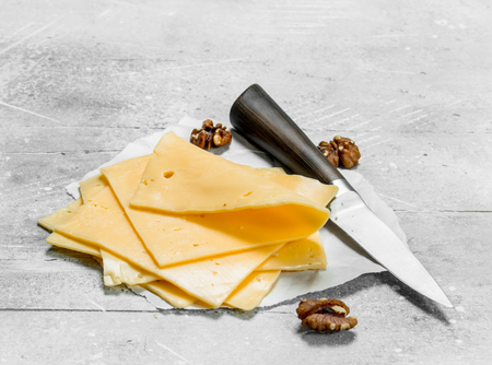 Thin slices of cheese with walnuts. On a rustic background. Фото со стока