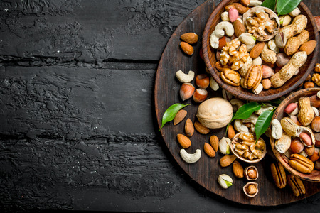 Assortment of different types of nuts in bowls. On black rustic background.