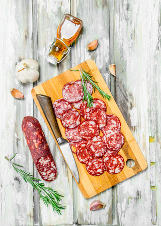 Sliced smoked salami with garlic and herbs. On a rustic background.