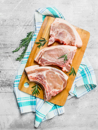 Raw pork steak on the bone with rosemary on the napkin. On a rustic background.