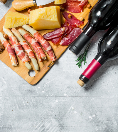Antipasto background. Various meat and cheese snacks with red wine. On a rustic background.