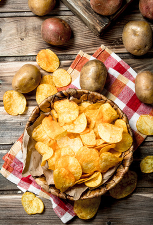 Potato chips in the basket. On a wooden background. Фото со стока