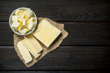 Butter on paper. On a wooden background.