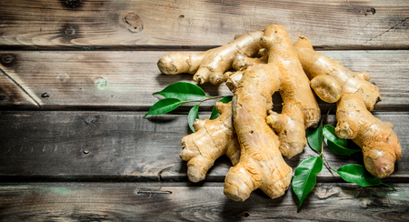 Fresh ginger with leaves. On wooden background 免版税图像