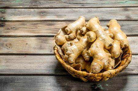Fresh ginger in the basket. On wooden background