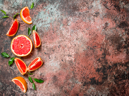 Fresh grapefruit with leaves. On rustic background