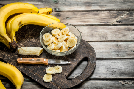 Bananas and banana slices in a plate on a black chopping Board with a knife. On a wooden background. Фото со стока