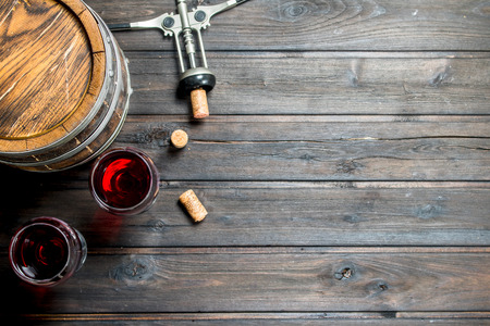 Wine background. A barrel of red wine with a corkscrew. On a wooden background.