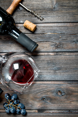 Wine background. Red wine with grapes. On a wooden background.