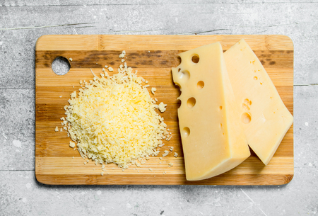 Fresh grated cheese on a wooden Board. On a rustic background. Фото со стока