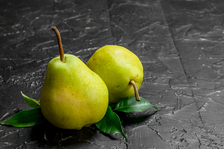 Fresh ripe pears with foliage. On rustic background Stock Photo