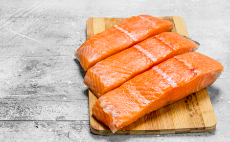 Raw salmon fish filet on cutting Board. On a rustic background. Фото со стока