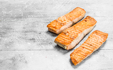Grilled salmon fillet. On a rustic background.