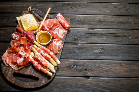 Antipasto background.A variety of meat snacks. On a wooden background.