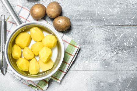 Peeled potatoes in a saucepan on napkin. On white rustic background