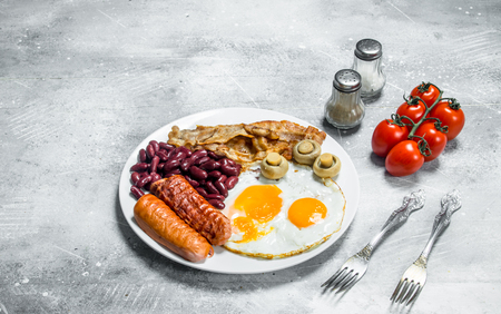 English breakfast. Fried eggs with sausages, bacon and beans. On a rustic background.