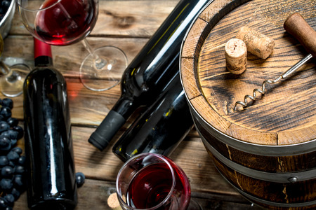 Wine background. Red wine with fresh grapes and an old barrel. On a wooden background.