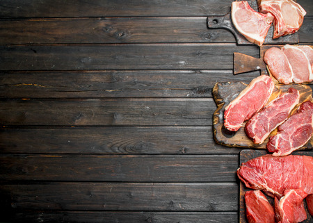 Raw meat. Different kinds of pork and beef meat. On a wooden background. Stockfoto