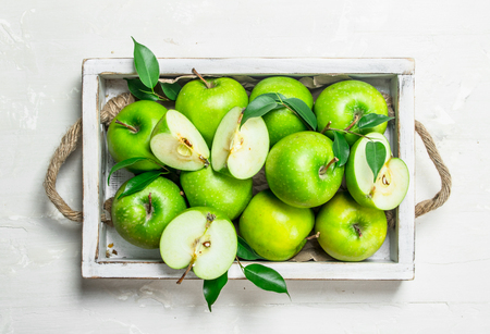 Green apples in a wooden tray. On white rustic background .