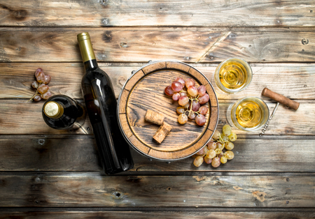 Wine background. White wine in an old barrel. On a wooden background