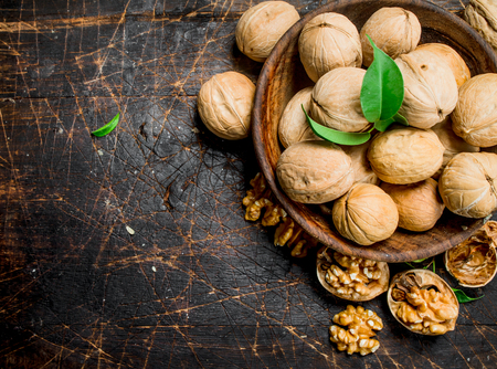 Walnuts in a bowl. On a wooden background.