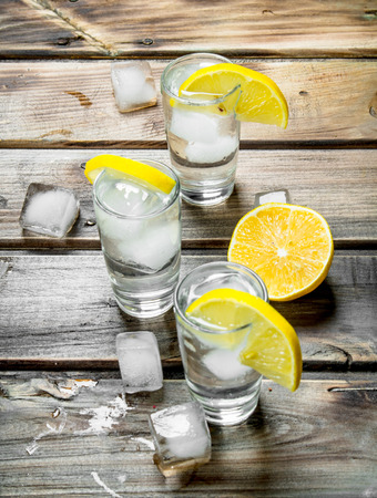 Vodka with ice in a shot glasses and slices of lemon. On wooden background