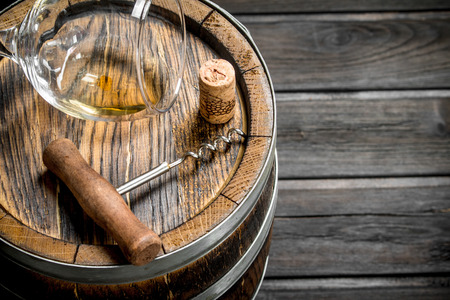 Wine background. An old barrel of white wine. On a wooden background.