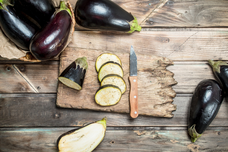 Pieces of eggplant on a cutting Board with a knife. On wooden background