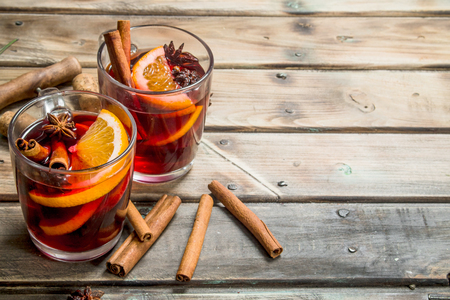 Mulled wine with aromatic seasonings. On a wooden background.