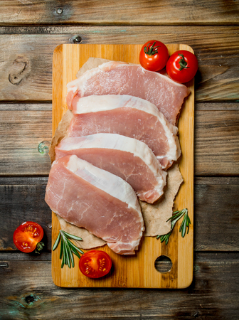 Raw pork steaks with tomatoes and rosemary. On a wooden background. Stock Photo