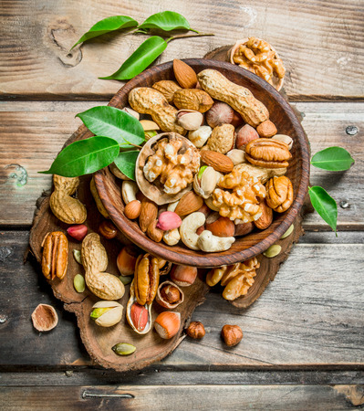 Different kinds of nuts in bowl with leaves. On a wooden background.