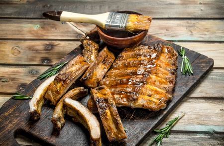 Chopped ribs grilled with a sauce. On a wooden background.