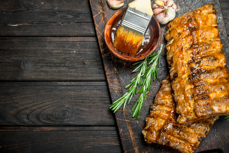 Grilled ribs with sauce, herbs and spices. On a wooden background. Banco de Imagens