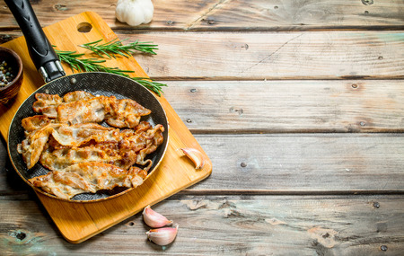 Fried bacon with garlic and spices. On a wooden background.