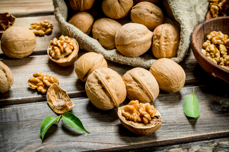 Walnuts in a bag . On a wooden background. Imagens