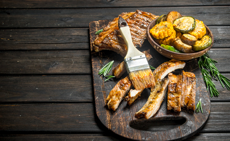 Grilled ribs and vegetables. On a wooden background. Imagens